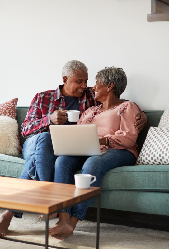 Couple sitting on couch with computer